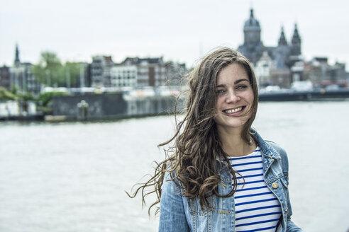 Netherlands, Amsterdam, portrait of smiling female tourist - RIBF000107