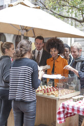 Woman buying pastries at food stall at city market - ZEF006584