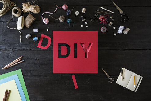 Craft materials and red cardboard with the word DIY on black wood - PDF000958