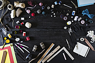 Arrangement of craft materials and tools on black wood - PDF000955