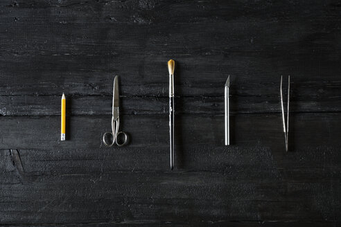 Row of different tools on black wood - PDF000946