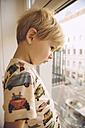 Blond little boy looking through window down to the street - MFF001639