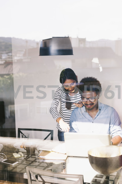 Young man and woman working with laptop and digital tablet at home office - EBSF000649