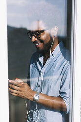 Smiling young man behind windowpane listening to music from smartphone - EBSF000652