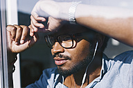 Young man with earbuds looking out of the window - EBSF000653