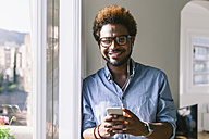 Portrait of smiling young man listening to music from smartphone - EBSF000656
