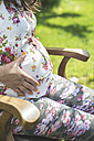 Pregnant woman sitting on wooden chair in a garden - DEGF000420