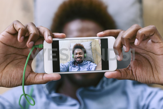 Young Afro American man lying on floor, taking selfie - EBSF000617