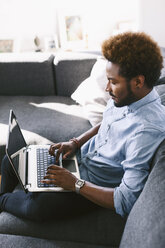 Young Afro American man sitting on couch, using laptop - EBSF000622