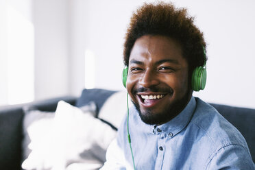 Young Afro American man wearing green headphones, laughing - EBSF000628