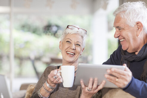 Senior couple with digital tablet and cup of coffee - ZEF005508