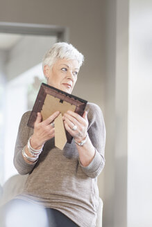 Senior woman holding picture frame looking at distance - ZEF005513