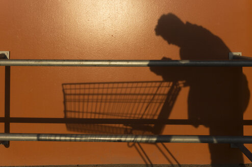 Shadow of a man leaning on empty shopping cart - ZMF000396