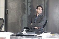 Businessman sitting at desk with arms crossed - ZEF005606