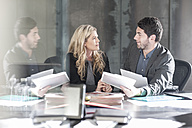 Businessman sitting face to face with woman at desk - ZEF005607