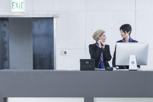 Two women behind reception desk in hotel lobby - ZEF005616