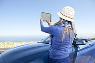South Africa, woman at a convertible taking pictures with a digital tablet - ZEF005643