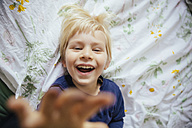 Smiling little boy lying on bed reaching out to camera - MFF001644