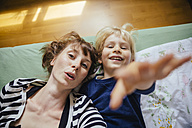 Mother and little son lying on bed reaching out to camera - MFF001645