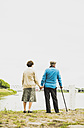 Back view of senior couple holding hands at water's edge - UUF004517