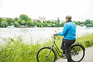Senior man with bicycle looking to the river - UUF004526