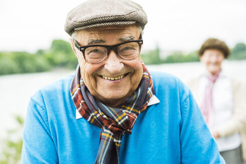Portrait of happy senior man with glasses and cap - UUF004529