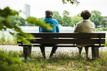 Back view of senior couple sitting on a bench - UUF004548