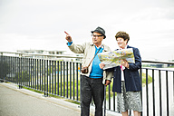 Senior couple with map standing on a bridge - UU004549