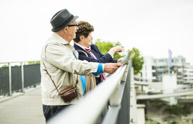 Senior couple with map standing on a bridge looking at view - UUF004552