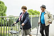 Senior couple with walking stick and wheeled walker - UUF004557