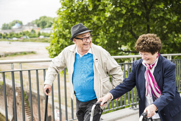 Laughing senior couple with walking stick and wheeled walker - UUF004560