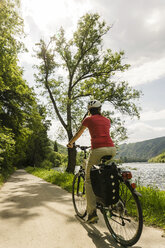 Germany, Cochem, woman riding bycicle along riverside of Moselle - UUF004569