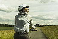 Woman riding bicycle at countryside - UUF004573