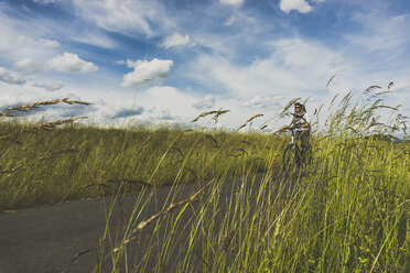 Woman riding bicycle in nature - UUF004578