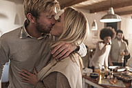 Young couple kissing in kitchen with friends in background - ZEF006276