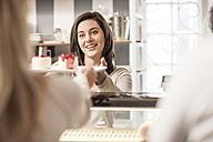 Young woman at cake counter serving cake to clients - ZEF006196