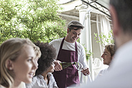 Waiter serving wine for friends lunching at restaurant - ZEF006197