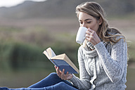 Woman with book drinking coffee on a jetty at lake - ZEF006170