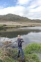 Young man fishing at a lake - ZEF005781