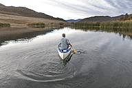 Back view of young man paddling on a lake - ZEF005786