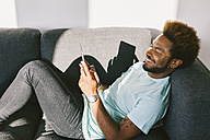 Young man at home reading messages on smart phone - EBSF000679