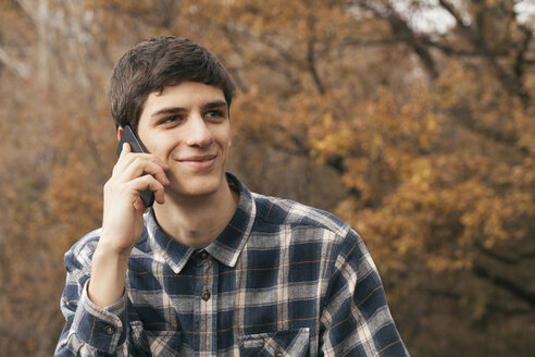 Portrait of smiling young man telephoning with smartphone in a park - BZF000163