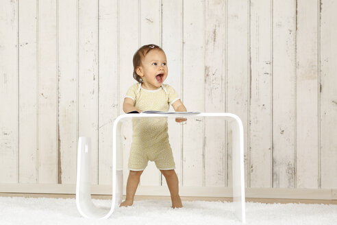 Baby girl standing behind modern side table - DRF001647
