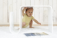 Baby girl crouching under modern side table - DRF001649
