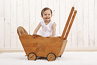 Portrait of smiling baby girl playing with wooden doll buggy - DRF001657