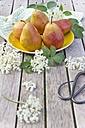 Pears on plate, elderflowers on wood - YFF000439