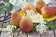 Pears with water drops on plate, elderflowers on wood - YFF000438