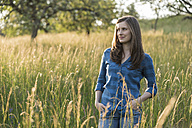 Young woman in a field in the evening - PAF001418