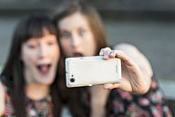 Two happy young women taking a selfie - PAF001420