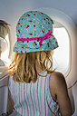 Little girl looking through window on board of an airplane - JFEF000676